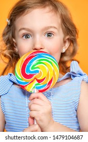 A portrait of a pretty girl with a lollipop in the studio over the yellow background. Kids, beauty, food, sweets.