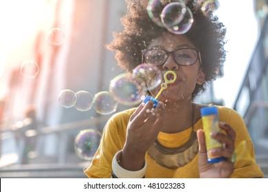 Portrait of a pretty girl making soap bubbles in the street