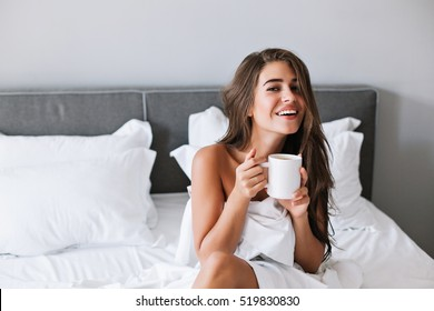 Portrait pretty girl with naughty shoulders drinking coffee on bed in the morning in apartment
