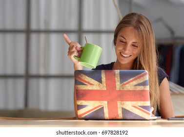 Portrait of pretty girl with nose piercing holding green cup of coffee while browsing laptop with British flag cover at table at home.