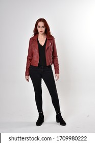 Portrait of a pretty girl with red hair wearing black jeans and boots with leather jacket.  full length standing pose on a studio background.