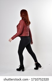 Portrait of a pretty girl with red hair wearing black jeans and boots with leather jacket.  full length standing pose with back to the camera a studio background.