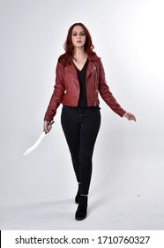 Portrait of a pretty girl with red hair wearing black jeans and boots with leather jacket.  full length standing pose holding knife a studio background.