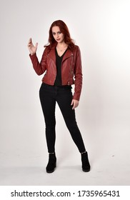 Portrait of a pretty girl with red hair wearing black jeans, red leather jacket and boots.  full length standing pose, isolated against a studio background