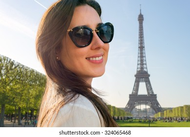 Portrait of a pretty girl smiling in Paris, France on Eiffel Tower background