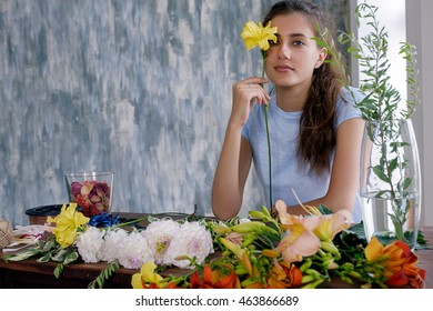Portrait of pretty girl at table with arranged flowers holding yellow lily at face.Copy space