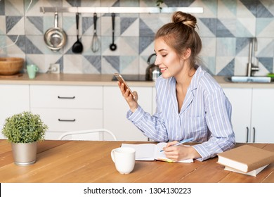 Portrait of pretty girl talking on mobile phone and writing down in notebook. Lovely lady in striped pyjamas with tied up hair sitting on kitchen. Modern interior concept