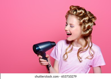 Portrait of a pretty girl teenager with curlers in her blonde hair holding hair  dryer. 2a8e950ac