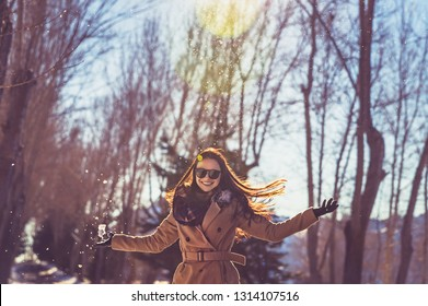 Portrait of a pretty girl wearing sunglasses and with pleasure spending time in bright sunny day in winter park, having fun like a child, happy wintertime vacation