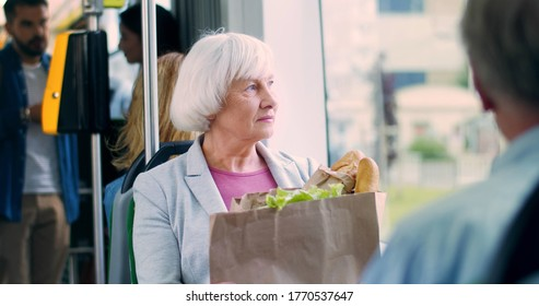 Portrait of pretty gray-haired Caucasian old woman with a big packet of vegetables and other food going home in public transportation.