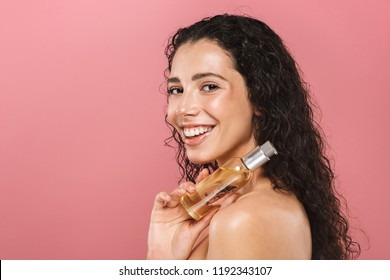 Portrait of pretty happy cheerful beautiful young woman posing isolated over pink background take care of her skin holding oil.