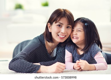 Portrait of pretty happy japanese mother play with her cute little daughter at home