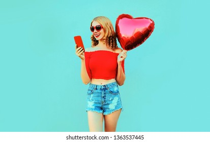 Portrait pretty happy smiling woman holding phone, red heart shaped air balloon on colorful blue background