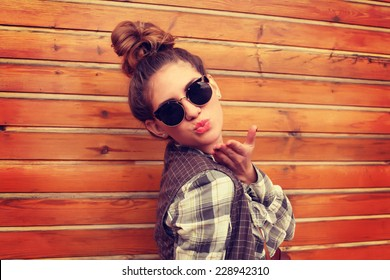 Portrait of pretty hipster girl in sunglasses, blowing kiss at the camera. Photo toned style instagram filters