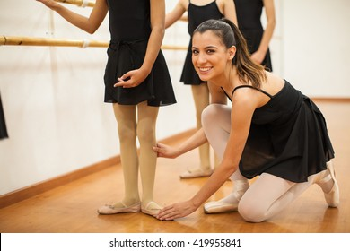 Portrait of a pretty Hispanic young teacher helping her students with their posture during dance class and smiling
