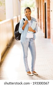 portrait of pretty indian university student standing by corridor on campus