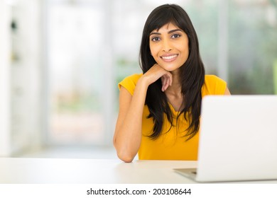 portrait of pretty indian woman sitting in front of laptop