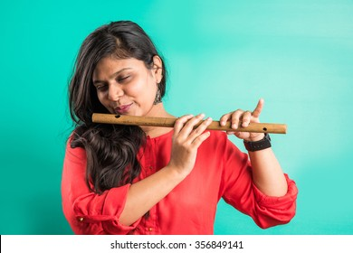 Portrait of pretty Indian/Asian Young girl musician playing Flute, isolated over green background