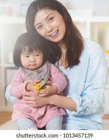 Portrait of a pretty japanese mother holding her cute baby daughter at home