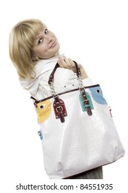 Portrait of pretty joyful girl holding stylish handbag