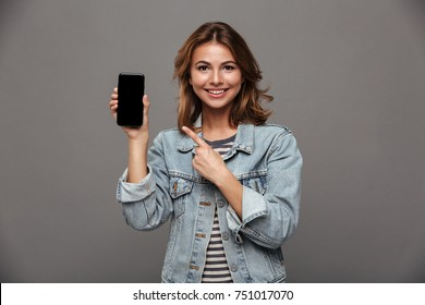 Portrait of a pretty joyful teenage girl dressed in denim jacket pointing finger at blank screen mobile phone isolated over gray background