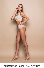 Portrait of pretty lady in her white underwear stands isolated on beige background