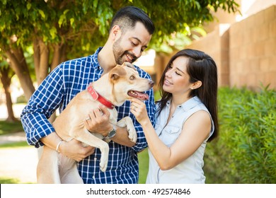 Portrait of a pretty Latin couple petting their dog at a park and having a good time together
