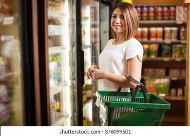 Portrait of a pretty Latin woman carrying a basket and buying groceries at a supermarket
