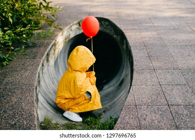Portrait of pretty litle girl in big adult oversized yellow raincoat with red balloon in hand standing and sitting against sewage tunnel pipe. Horror movie concept. Funny child posing in summer day