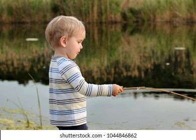 Portrait of a pretty little 3-year old boy playing with wood stick like a fishing tackle in reeds on the meadow, sunny day, happy family weekend, early spring outdoor