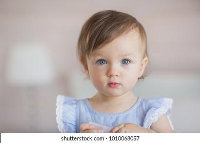 Portrait of a pretty little baby girl in a blue dress