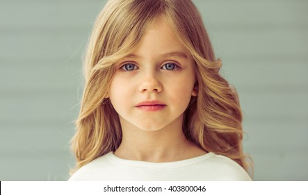 Portrait of pretty little blonde girl with beautiful big eyes looking at camera