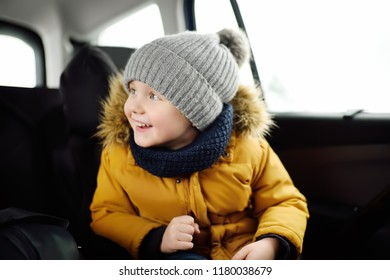 Portrait of pretty little boy sitting in car seat during roadtrip or travel. Family car travel with kids. Child transportation safety