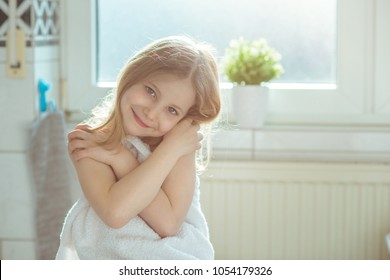 Portrait of pretty little child girl with white towel after shower  in bright bathroom at home