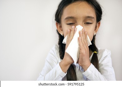 A portrait of a pretty little girl blowing her nose on a white background.