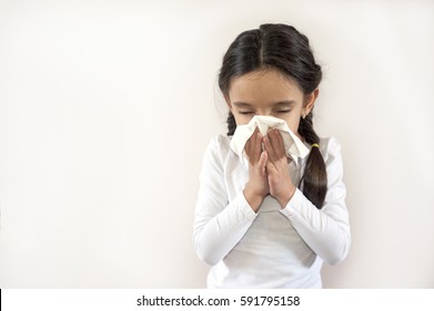 A portrait of a pretty little girl blowing her nose on a white background with copy space.