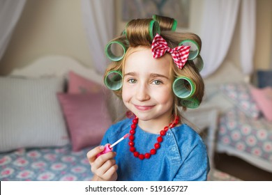 Portrait of pretty little girl with a curlers and lipstick at hand