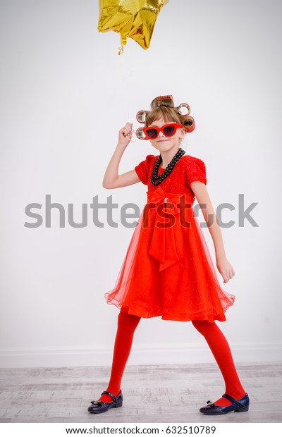 Portrait of a pretty little girl with curlers in her hair wearing beautiful red dress. Kid's fashion. Party, festive style.
