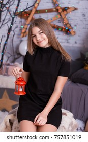 Portrait of pretty little girl with decorative vintage lamp with candle over background with bokeh; Christmas studio decoration