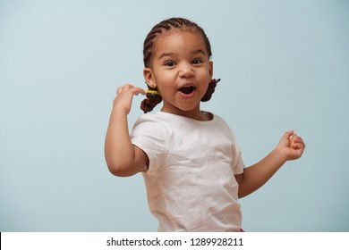 Portrait of pretty little girl dressed for sport. She's holding a tangerine slice in one hand. Looking very exited. Pale blue background.