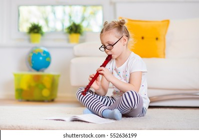 Portrait of pretty little girl with flute on floor at home