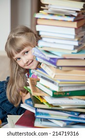 Portrait of a pretty little girl hiding behind a stack of books