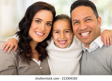 portrait of pretty little girl hugging her parents at home