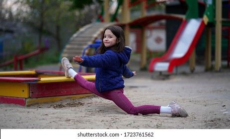 Portrait of a pretty little girl with long loose hair in blue jacket in a park on the playground. Young gymnast sitting in a twine position