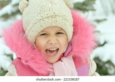 Portrait of pretty little girl playing with snow