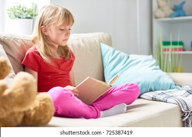 Portrait of pretty little girl reading book sitting cross legged on comfortable couch in cozy living room at home