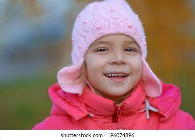 Portrait of pretty little girl in red jacket in autumn park.
