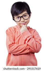 Portrait of pretty little girl standing in the studio while wearing round glasses and look at the camera