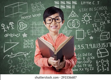 Portrait of pretty little girl standing near the chalkboard in the class while reading a book