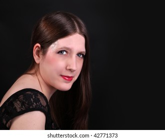 Portrait of a pretty long haired brunette woman with red lipstick and glitter on her temples dressed in sild and velvet (softening effect)